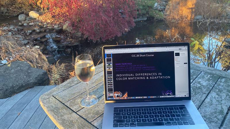 wine glass next to a laptop outside