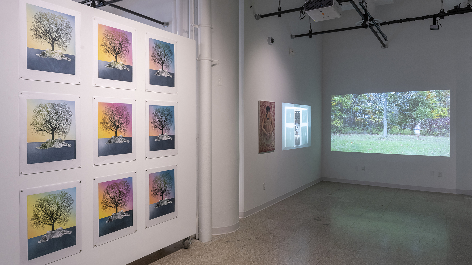 A wall displays paintings and video.